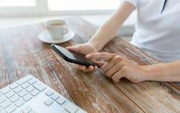 Fermez-vous des mains avec le téléphone intelligent à la table de bureau Image stock