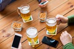 Fermez-vous des mains avec les smartphones et la bière à la barre Photographie stock libre de droits