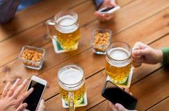 Fermez-vous des mains avec les smartphones et la bière à la barre Photos libres de droits