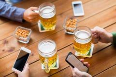 Fermez-vous des mains avec les smartphones et la bière à la barre Images stock