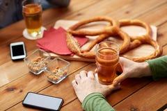 Fermez-vous des mains avec les smartphones et la bière à la barre Photos stock