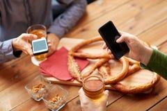 Fermez-vous des mains avec les smartphones et la bière à la barre Image libre de droits
