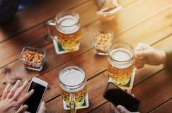 Fermez-vous des mains avec les smartphones et la bière à la barre Image stock