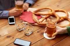 Fermez-vous des mains avec les smartphones et la bière à la barre Photo stock
