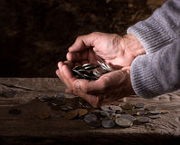Fermez-vous des mains caucasiennes et de la pile de vieil homme de vieilles pièces de monnaie Images stock
