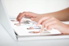 Fermez-vous des mains choisissant des photos sur un ordinateur portable futuriste Photographie stock