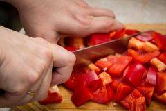 Fermez-vous des mains coupant des légumes avec un couteau images stock