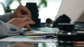 Fermez-vous des mains courantes de photographe travaillant sur l'ordinateur portable, décalage de foyer de lentille de photograph banque de vidéos