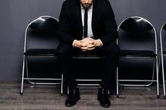 Fermez-vous des mains croisées du jeune homme bel s'asseyant sur la chaise et attendant son tour dans le hall de bureau images libres de droits