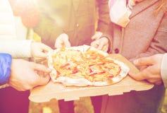 Fermez-vous des mains d'amis mangeant de la pizza dehors Photo libre de droits