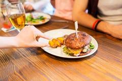 Fermez-vous des mains d'amis partageant l'hamburger à la barre Photos stock