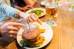 Fermez-vous des mains d'amis partageant l'hamburger à la barre Photographie stock libre de droits