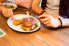 Fermez-vous des mains d'amis partageant l'hamburger à la barre Photos libres de droits