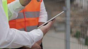 Fermez-vous des mains d'architecte utilisant le comprimé près du chantier de construction L'homme de constructeur et d'architecte banque de vidéos
