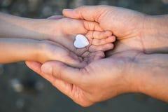Fermez-vous des mains d'enfant et d'homme avec le coeur Photo stock