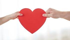 Fermez-vous des mains d'enfant et de mâle tenant le coeur rouge Image stock