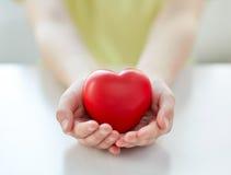 Fermez-vous des mains d'enfant tenant le coeur rouge Photo libre de droits