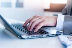 Fermez-vous des mains d'homme d'affaires dactylographiant sur l'ordinateur portable Photographie stock libre de droits