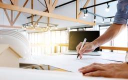 Fermez-vous des mains d'ingénieur esquissant un projet de construction avec l'ordinateur portable sur le lieu de travail photographie stock