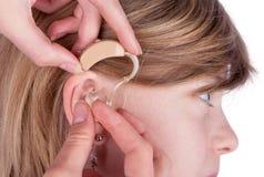 Fermez-vous des mains d'un Audiologist insérant une prothèse auditive dans l'ea images stock