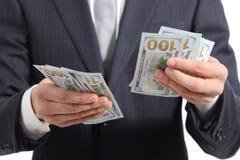 Fermez-vous des mains d'un homme d'affaires comptant l'argent Images stock