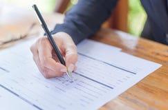 Fermez-vous des mains d'une femme d'affaires dans la signature ou le wr d'un costume Images stock