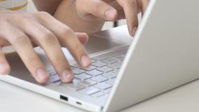 Fermez-vous des mains dactylographiant sur l'ordinateur portable dans le bureau banque de vidéos