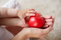Fermez-vous des mains de bébé et de mère avec le coeur rouge Image stock