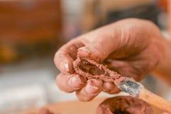 Fermez-vous des mains de ceramist de femme cleanning l'outil après avoir travaillé à la sculpture sur la table en bois dans l'ate photographie stock libre de droits