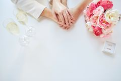Fermez-vous des mains de couples et des anneaux de mariage lesbiens Image stock