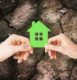 Fermez-vous des mains de couples tenant la maison verte Image stock