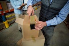 Fermez-vous des mains de directeur attachant du ruban adhésif vers le haut d'une boîte en carton Image stock