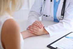 Fermez-vous des mains de docteur rassurant son patient féminin Photographie stock libre de droits