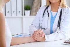Fermez-vous des mains de docteur rassurant son patient féminin Photos stock