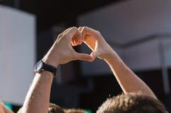 Fermez-vous des mains de fan montrant le coeur au concert Image libre de droits
