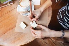 Fermez-vous des mains de femme écrivant différents autocollants de notes par le crayon en bois Jeune belle femme dessinant le div Images stock