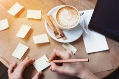 Fermez-vous des mains de femme écrivant différents autocollants de notes par le crayon en bois Jeune belle femme dessinant le div Image stock