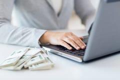 Fermez-vous des mains de femme avec l'ordinateur portable et l'argent Photos libres de droits