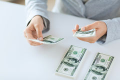 Fermez-vous des mains de femme comptant argent de dollar US Images stock