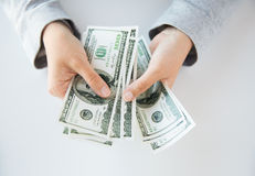 Fermez-vous des mains de femme comptant argent de dollar US image libre de droits