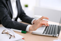 Fermez-vous des mains de femme d'affaires dactylographiant sur l'ordinateur portable dans le bureau coloré par blanc Photographie stock libre de droits