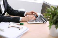 Fermez-vous des mains de femme d'affaires dactylographiant sur l'ordinateur portable dans le bureau coloré par blanc Photographie stock