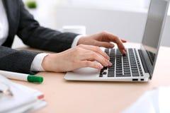 Fermez-vous des mains de femme d'affaires dactylographiant sur l'ordinateur portable dans le bureau coloré par blanc Photos libres de droits