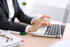 Fermez-vous des mains de femme d'affaires dactylographiant sur l'ordinateur portable dans le bureau coloré par blanc Photo stock