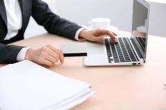 Fermez-vous des mains de femme d'affaires utilisant la carte de crédit et l'ordinateur portable Image libre de droits