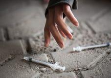 Fermez-vous des mains de femme d'intoxiqué et des seringues de drogue photographie stock libre de droits