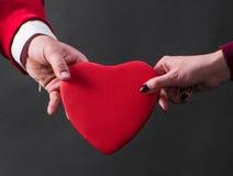 Fermez-vous des mains de femme et d'homme avec le coeur Photo stock