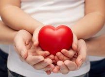 Fermez-vous des mains de femme et de fille tenant le coeur Images libres de droits