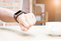 Fermez-vous des mains de femme La femme vérifient sa montre intelligente Dans le matin photographie stock libre de droits