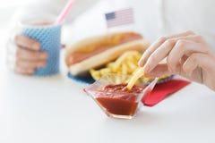 Fermez-vous des mains de femme mangeant sur la nourriture américaine Photo libre de droits